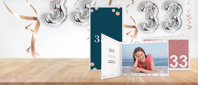 Abbildung von Geburtstagseinladungen in Rosa und Dunkelgrau. Bedruckt mit Foto, Text und der Zahl 33. Im Hintergrund haengen Schleifenband und silberne Luftballons.