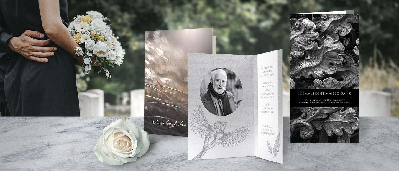 Abbildung von hellen und dunklen Trauerkarten, gestaltet mit Foto und Text. Daneben liegt eine weisse Bluete und im Hintergrund sind Baeume und Graeser zu sehen.