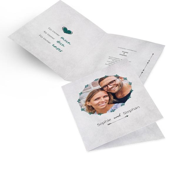 Graue Hochzeitseinladungen selbst gestalten in Hoch mit rundem Foto, Namen und Pfeil. Innen links ist ein Schriftzug und rechts ist Platz fuer persoenliche Worte.