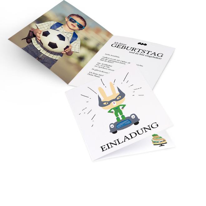 Abbildung einer Einladung zum Kindergeburtstag fuer Jungs im Hochformat, mit einem Superheld-Hasen in Blau-Grau. Innenseiten mit Platz fuer Foto links und Text rechts.