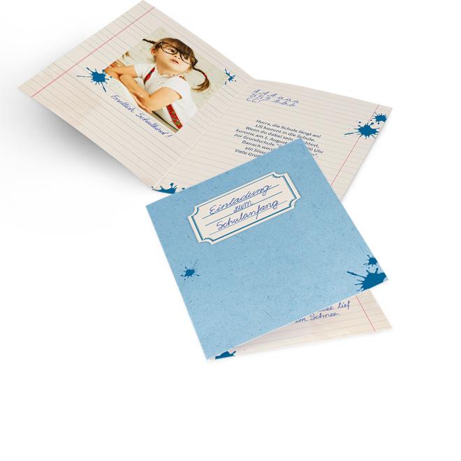 Abbildung von blauen Einschulungskarten im Hochformat als Hausaufgabenheft, mit Schriftfeld und Tintenklecksen. Innenseiten bieten Platz fuer Foto links und Text rechts.