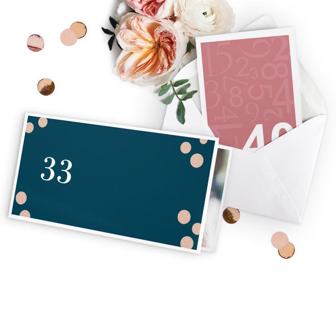 Abbildung von Geburtstagseinladungen in Rosa und Dunkelgrau. Bedruckt mit Foto, Text und Wunschzahl. Im Hintergrund liegen Konfetti und weiss-rosane Blueten.