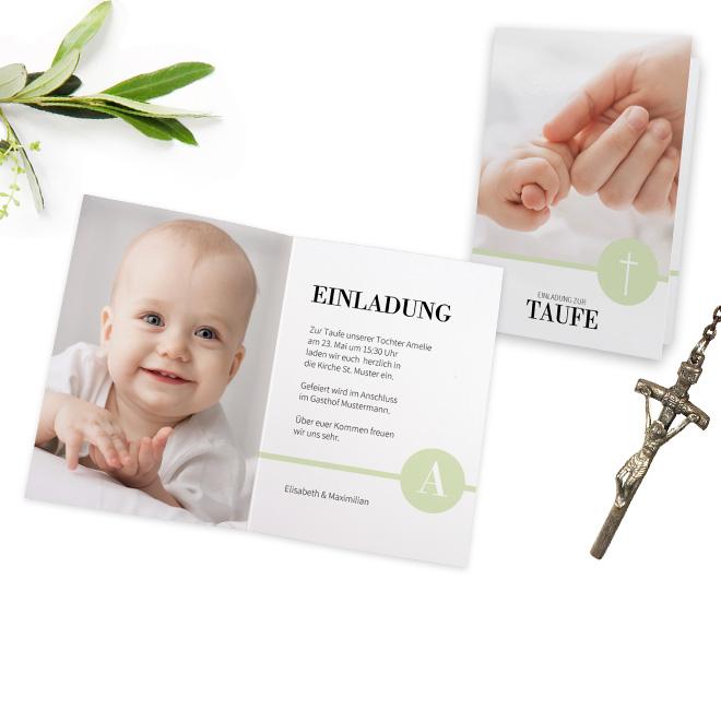 Abbildung einer Taufeinladung mit Verzierungen und grossem Foto auf der linken Innenseite. Daneben liegt ein silbernes Kreuz und gruene Zweige.