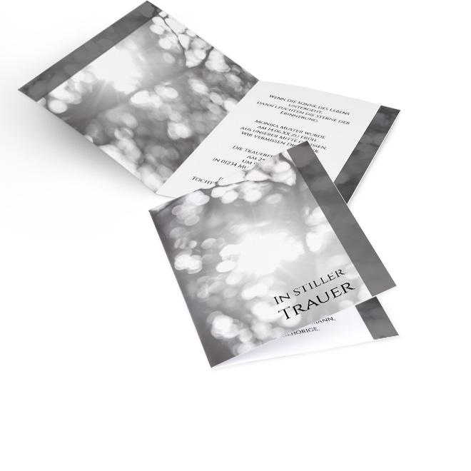 Abbildung schwarz-weisser Einladung zur Beerdigung in Hoch, mit Baumkrone und Schriftzug: In stiller Trauer. Innenseiten mit Baumkrone links und Platz fuer Text rechts.