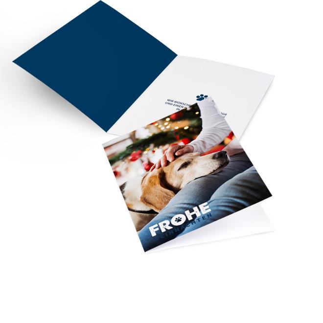 Blau-weisse nostalgische Weihnachtskarten im Hochformat mit vollflaechigem Foto und Schriftzug FROHE WEIHNACHTEN. Rechte Innenseite mit kleiner Pfote und Platz fuer Text.